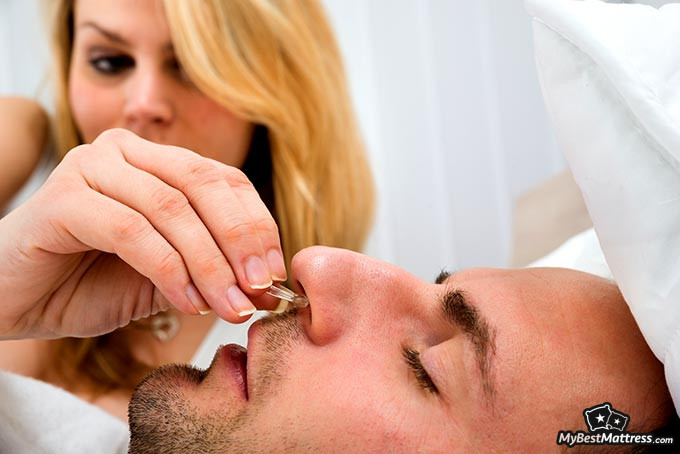 Anti-snoring devices: a man inserting an anti-snoring device into his nose.