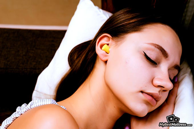 Best earplugs for sleeping: a woman sleeping with earplugs in her ears.
