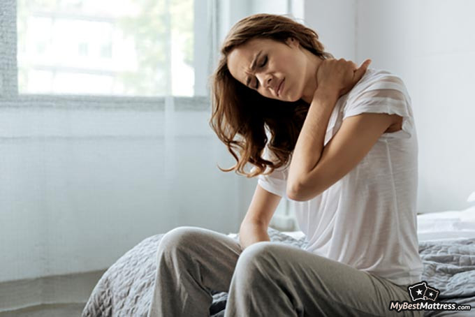 Best pillow for neck pain: woman having cramps in the neck region.