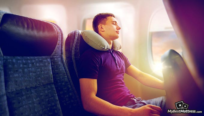 Best travel pillow: a man sleeping in an airplane with a travel pillow.