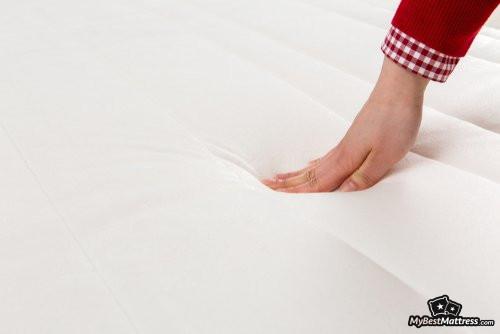 Puffy mattress reviews: a woman's hand pushing down on a mattress.