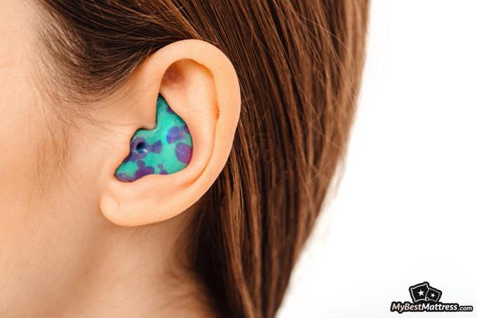 Best earplugs for sleeping: woman with earplugs in her ears.